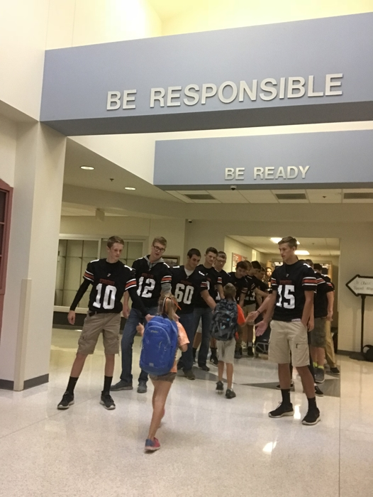 Football players greeting student
