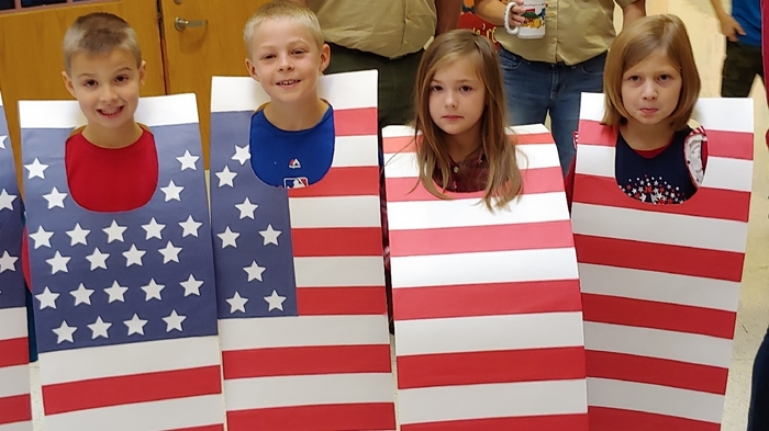 2nd grade students dressed as a flag