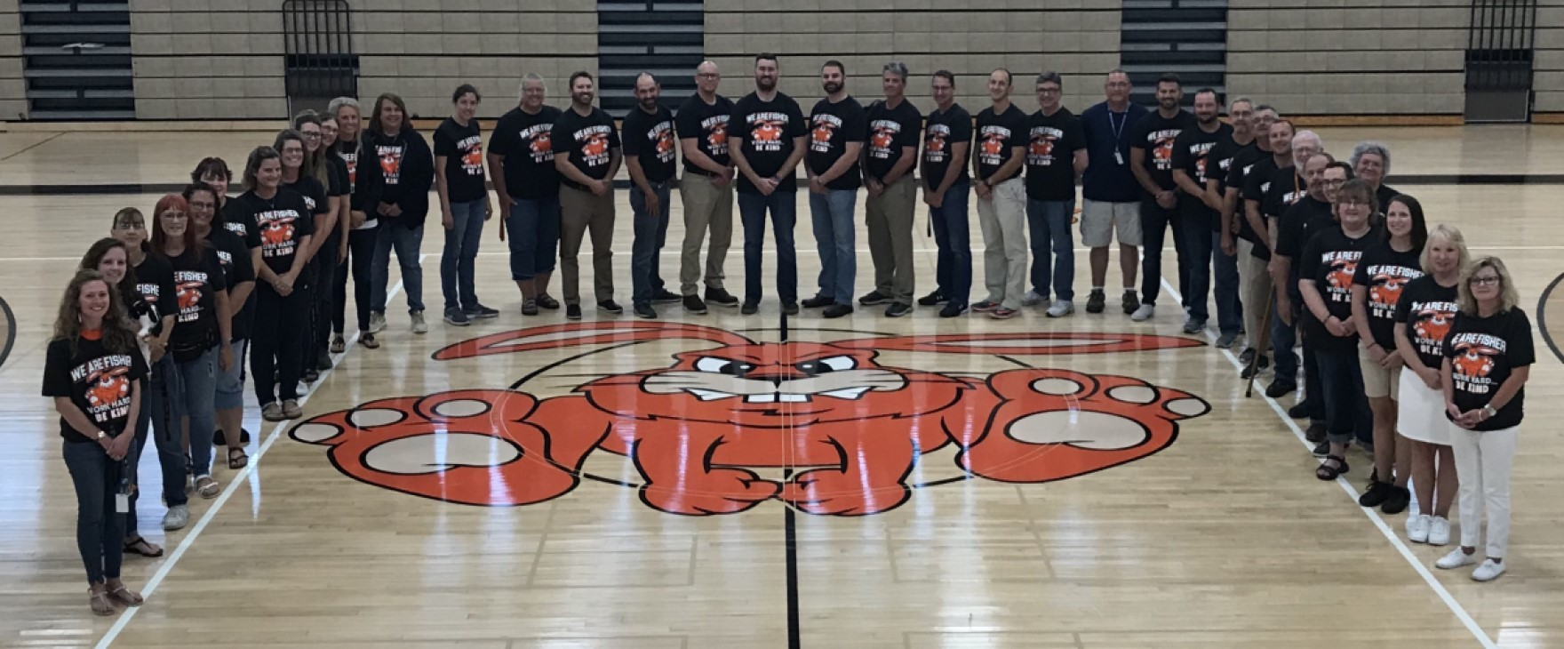 Staff standing around the Bunny Logo in the High School Gym.